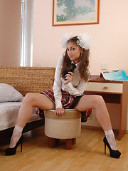 Glamorous teen with two big white ribbons in her magnificent hair stripping school uniform.
