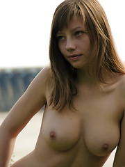 Enchanting girl showing great breasts and neatly trimmed pussy outdoor against the dam.