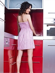 With curly hair in loose braids, wearing pink, sexy dress matching red, pearl necklace, Ralina evokes a sweet and young maiden, as strips and poses sensually with wide open poses at the kitchen and over the dining table.