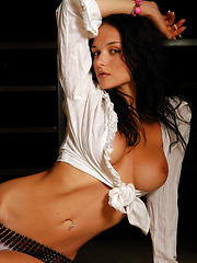 Super model Jenya in a studio shoot with a white top and a chair is smoking.