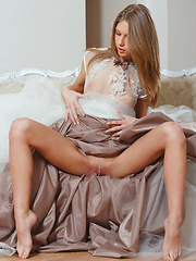 Katherine naughtily lifts her dress skirt to reveal her smooth, shaven labia, before getting naked on top of the sofa.