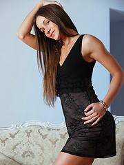 Cute brunette girl undressing in the bedroom