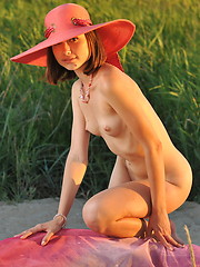 Beautiful shapely charmer in a hat with a wide brim showing tits and pussy on the seaside.