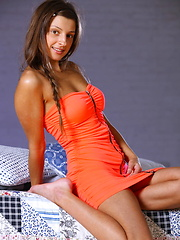 Malena, with her tempting gaze, beautiful puffy breasts, and slender physique strips her sexy orange dress baring her delectable assets in front of the camera.