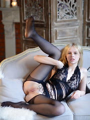 Angelika D with her innocent face yet seductive look as she poses in her sheer black lingerie and stockings