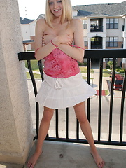 Blonde teen Skye Model teases out on the patio in a little pink top with matching pink thong panties
