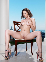 Sultry siren Anita E wearing nothing but her sleek, stiletto sandals, posing seductively in the balcony